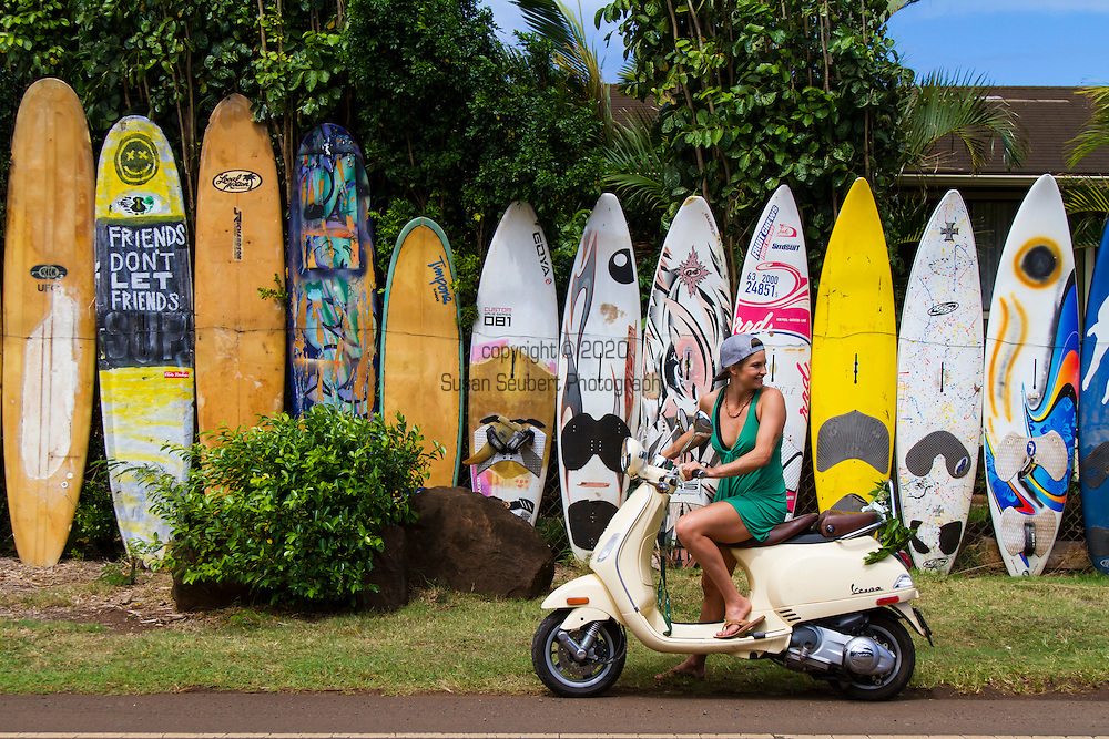 Olympic skier Julia Mancuso riding her vespa scooter by a fence made out of old surf and windsurfing boards near her home in Maui, Hawaii