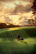 A golfer and his caddy prepare for a shot on a golf course lit by the rising sun