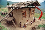 New house blessing in the village of Shingkhey, Bhutan. Monks perform a ceremony that includes music and chanting. The whole village is treated to a special meal inside afterward. From Peter Menzel's Material World Project.