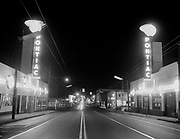 Y-541015-01. Lighting on Hawthorne Ave. from SE 6th looking east. Billingsley Pontiac, 635 SE Hawthorne. Just past the Pontiac dealerships is the intersection of 7th. On the left is Oregon Parts Co., at 711 SE Hawthorne. On the right is Hawthorne Electronics at 700 SE Hawthorne. Night view. October 15, 1954.