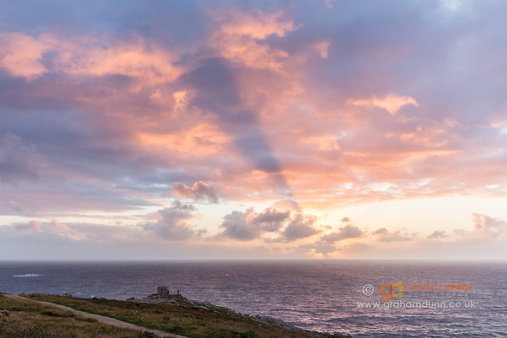 A dramatic cloud shadow over the Atlantic Ocean and Mayon Cliff Lookout, Sennen Cove, Cornwall. Summer sunset in England, UK. July.