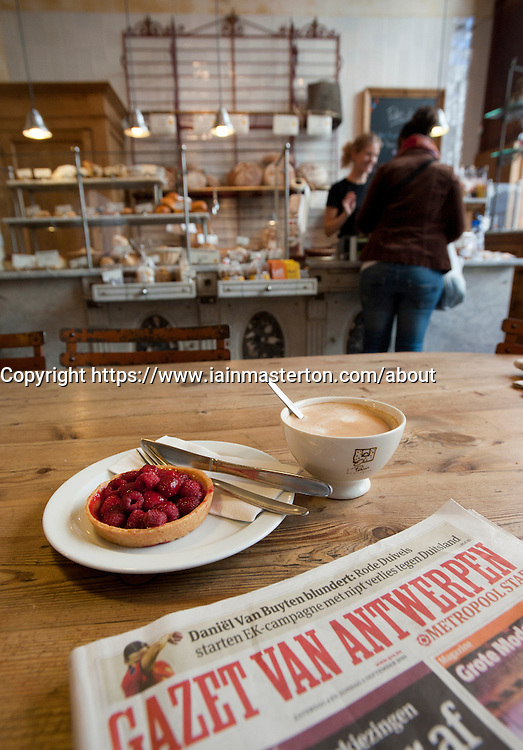 Detail of coffee ,cake, and local newspaper in traditional bakers shop and cafe in central Antwerp in Belgium