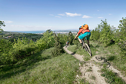 Young biker jumping in mid-air while riding through narrow trail