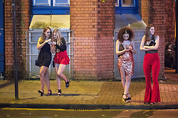 """© Licensed to London News Pictures . 16/12/2017. Manchester, UK. Two pairs of women wait on the pavement at Deansgate Locks . Revellers out in Manchester City Centre overnight during """" Mad Friday """" , named for historically being one of the busiest nights of the year for the emergency services in the UK . Photo credit: Joel Goodman/LNP"""