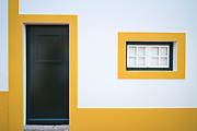 Typical colours of Evora - white and yellow geometric box house with dark green front door in street in Evora, Portugal