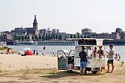 Nederland, nijmegen, 25-7-2019Mensen trekken massaal naar de oevers van de waal en de spiegelwaal in het rivierpark aan de overkant van Nijmegen . De recordwarmte drijft mensen naar het water . Om niet helemaal te verbranden liggen veel badgasten in de schaduw van de spoorbrug .Foto: Flip Franssen