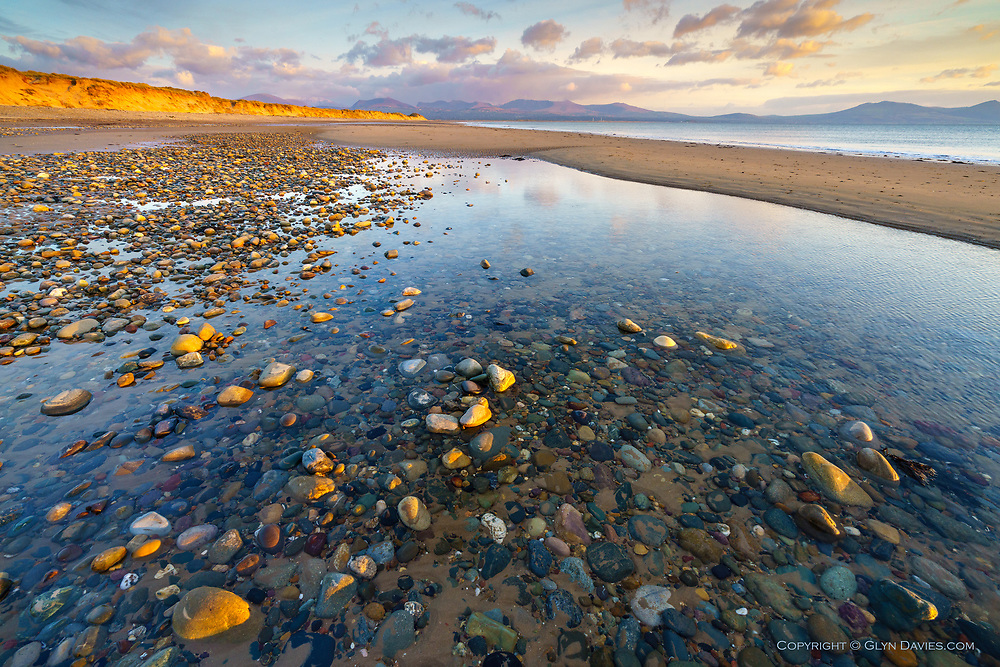 A quick detour down to Llanddwyn to photograph a huge dark snow-cloud floating over Ynys Mon, but although a sprinkling of delicate snowflakes blew past me, the snow-clouds simply disappeared, a calm sunset taking its place. The multitude of colours within the mass of pebbles in this area is quite something to consider. The wonder of geology.