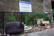 Fly-tipping left on a Lewisham street beneath a council sign threatening fines ad/or imprisonment. cardboard boxes, childrens' toys, a sofa and plastic can be seen on the ground under the sign - a blatant disregard for local bylaws and rules against the dumping of refuse and garbage. Enforcement officers operate in this area and they have the power to enforce penalties of up to £50,000 and/or six months imprisonment - a threat but obviously not enough of a deterent.