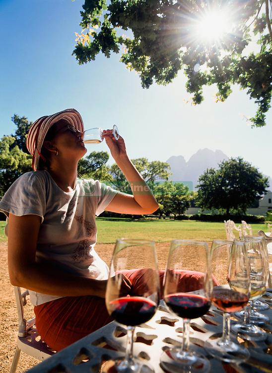 Woman tasting wine under oak tree at Boschendal wine estate (Credit Image: © Axiom/ZUMApress.com)