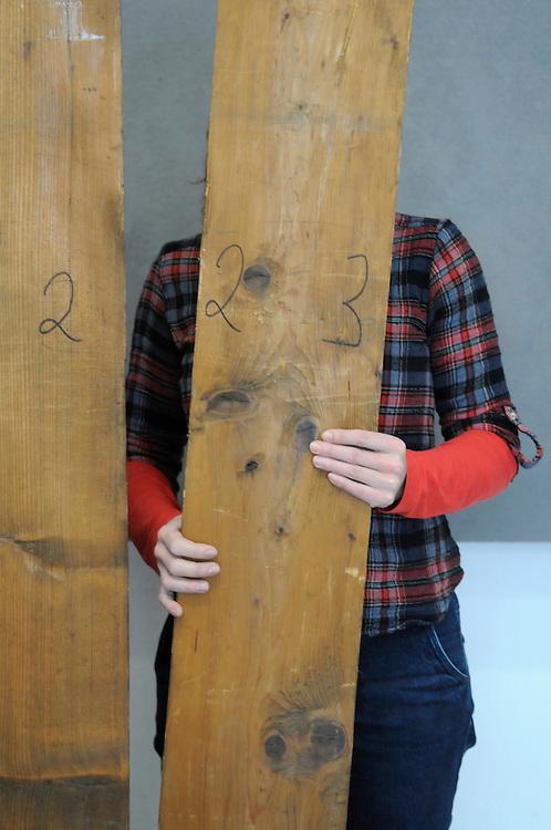 Frau beim Zusammenbau eines alten Schranks | woman holds a board of an old cupboard