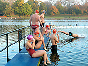The start of the Serpentine Swimming Club Saturday morning swimming race, Hyde Park, London, UK. The Serpentine Lake is situated in Hyde Park, London's largest central open space. The Serpentine Swimming Club was formed in 1864 'to promote the healthful habit of bathing in open water throughout the year'.  Its headquarters were beneath an old elm tree on the south side of the lake, a wooden bench for clothing being the only facility.  At this time London was undergoing rapid expansion and Hyde Park was now in the centre of a densely populated built up area and provided a place of relaxation to its urbanised masses. Now, the club has its own (somewhat spartan) changing facilities and members are  permitted by the Royal Parks to swim in the lake any morning before 09:30.  They race every Saturday morning throughout the year, regardless of the weather.