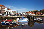Fishing boats moored at the quayside in the harbour in Whitby, a seaside town, port in the county of North Yorkshire, originally the North Riding. Situated on the east coast at the mouth of the River Esk. Tourism started in Whitby during the Georgian period and developed. Its attraction as a tourist destination is enhanced by its proximity to the high ground of the North York Moors, its famous abbey, and by its association with the horror novel Dracula. Yorkshire, England, UK.