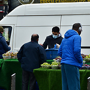 During the coronavirus in UK lockdown people queue to buy fruit at the the fruits stall,on 28 March 2020, at Walthamstow Market, London.