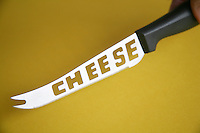 Cheese knife against a yellow background