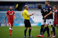 Captain Danny Shittu of Millwall having a heated discussion with Match Referee Scott Duncan for a foul award to Cardiff City. Skybet football league championship match , Millwall v Cardiff city at the Den in Millwall, London on Saturday 25th October 2014.<br /> pic by John Patrick Fletcher, Andrew Orchard sports photography.