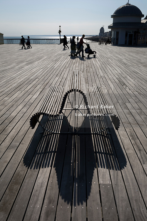 The figures of visitors and the shadows of a bench on Hastings Pier, on 29th April 2017, at Hastings, East Sussex, England.