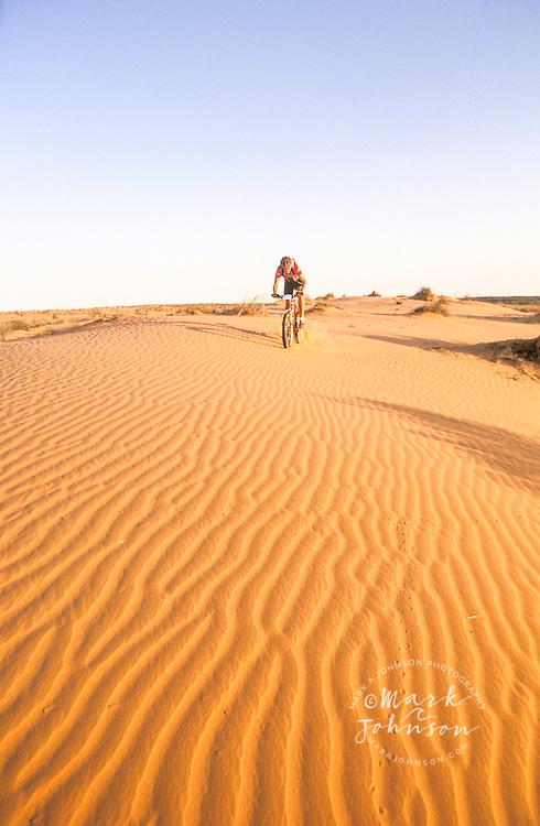 Australia, Simpson Desert, mountain biker riding on sand dune ****Model Release available