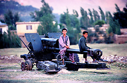 Afghanistan/Badakhshan 28 July 2005..Children play with an piece of artillery formally used during warfare