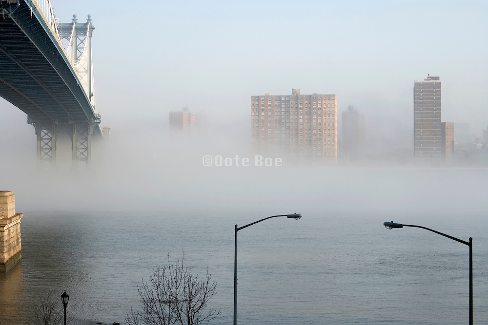 Manhattan bridge and East river in early morning fog seen from Brooklyn site
