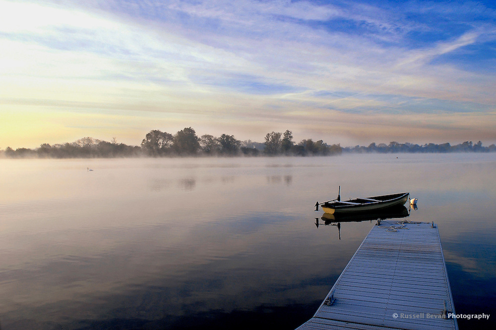 A rowing boat on a lake in the Cotswold Water Park at sunrise