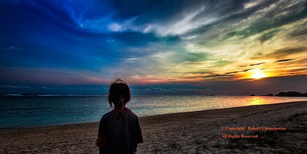 Sunset of Hope: A young girl facing an inevitably dark life of poverty and disappointment, stands alone gazing upon the beauty of a tropical sunset, as distant and transient as hope, Tanjung Pedau Beach, Lombok Indonesia.