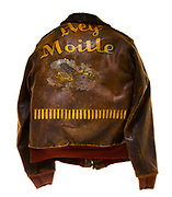 """This type A-2 flight jacket belonged to Merle Childress, a ball turret gunner attached to the 570th Squadron of the 390th Bomb Group. Childress flew 25 missions over Europe, which is signified by the 25 bombs painted on the bottom portion of the back of the jacket. Above the bombs is the name of his plane """"Hey Moitle"""" written above a painting of a B-17 flying in front of a cloud. The front of the jacket is plain, but there is a circular pattern on the left breast where the squadron patch would have been sewn to the jacket."""