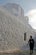 Greece, Amorgos, Cyclades: A woman walking along the streets of Amorgos