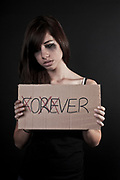 crying Heartbroken teen with a sign modified from FOREVER to OVER