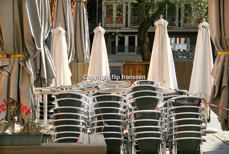 Nederland, Nijmegen, 30-4-2020 De horeca is al enkele weken gesloten vanwege de coronadreiging en veel ondernemers willen dat de regering het normale dagelijks leven weer langzaam laat opstarten . Opgestapelde stoelen met parasols . Unlock,beperkende,beperkingen, opheffen,versoepelen,versoepeling , opengooien. Foto: Flip Franssen