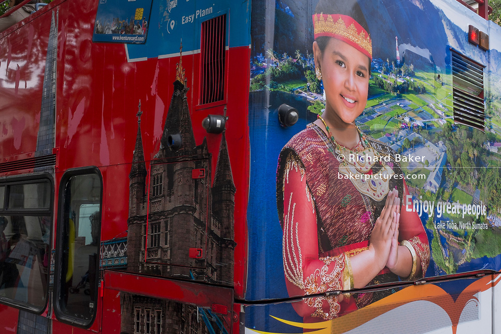Detail of the ads representing London's Tower Bridge and the beauty of a North Sumatran lady from Indonnesia, on the rear of a London tour bus, on 12th June 2018, in London, England.