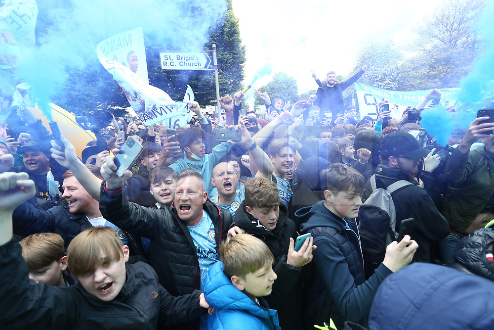 © Licensed to London News Pictures. 23/05/2021. Manchester, UK.  Man City fans go wild as the team bus arrives at the Etihad. Thousands of supporters have gathered at the Etihad Stadium to celebrate winning their 5th Premier League title in 10 years.  Photo credit: Adam Vaughan/LNP