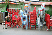A man sitting amidst piles of red and blue plastic chairs in the streets of Yangon on 16th May 2016 in Myanmar