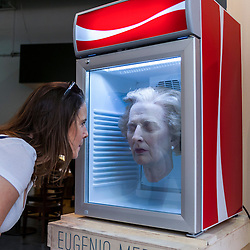 """© Licensed to London News Pictures. 23/05/2015.  London, UK. BLUE ICE LADY... With the recent UK general election still fresh in people's minds, a piece entitled """"Always Thatcher"""" by Eugenio Merino catches the eye at Art15, a global art fair, currently taking place at Kensington Olympia. The head is suspended in a beverage refrigerator, has a price tag of £17,000 and is being presented by the Unix gallery of New York.  Photo credit : Stephen Chung/LNP"""