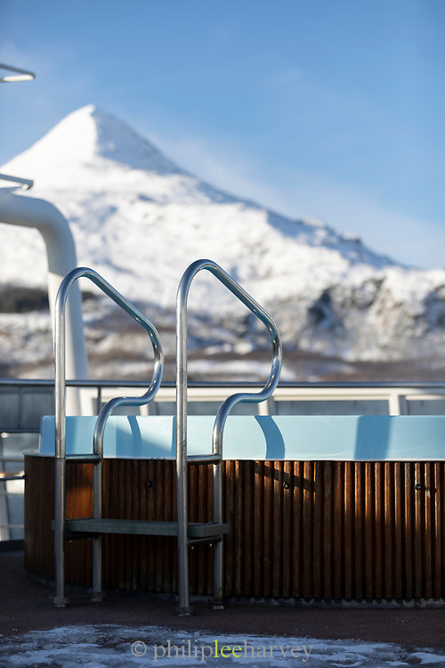 Hot tub on ship with view of mountain covered in snow, Nesna, Norway