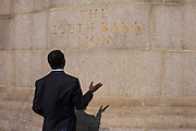 A religious man seemingly at prayer beneath the lion on the Southbank, south side of Westminster Bridge,