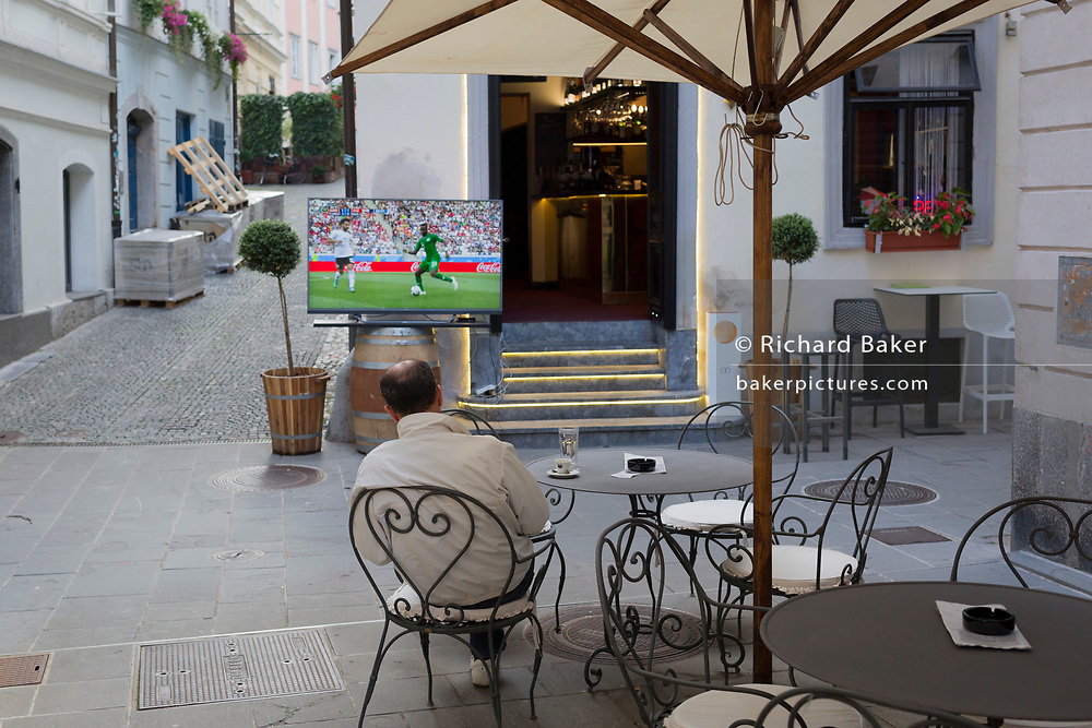 A solitary sports fan watches a World Cup 2018 game on TV, in the Slovenian capital, Ljubljana, on 25th June 2018, in Ljubljana, Slovenia.