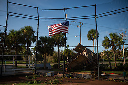 September 11, 2017 - Florida, U.S. - A tattered American flag is seen in front of damage and debris following Hurricane Irma at Marco Island. Irma made landfall at Marco Island as a category 3 hurricane, according to the National Hurricane Center. (Credit Image: © Loren Elliott/Tampa Bay Times via ZUMA Wire)