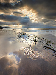 Patterns of light in the sky reflect the patterns in the sand left by the receding tide at Lilstock Beach, Somerset