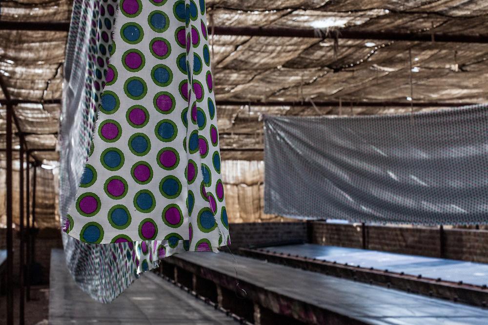 A spot patterned sari hang dries after screen printing.
