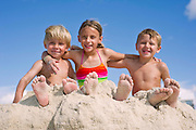 Three kids embrace while sitting on the beach.