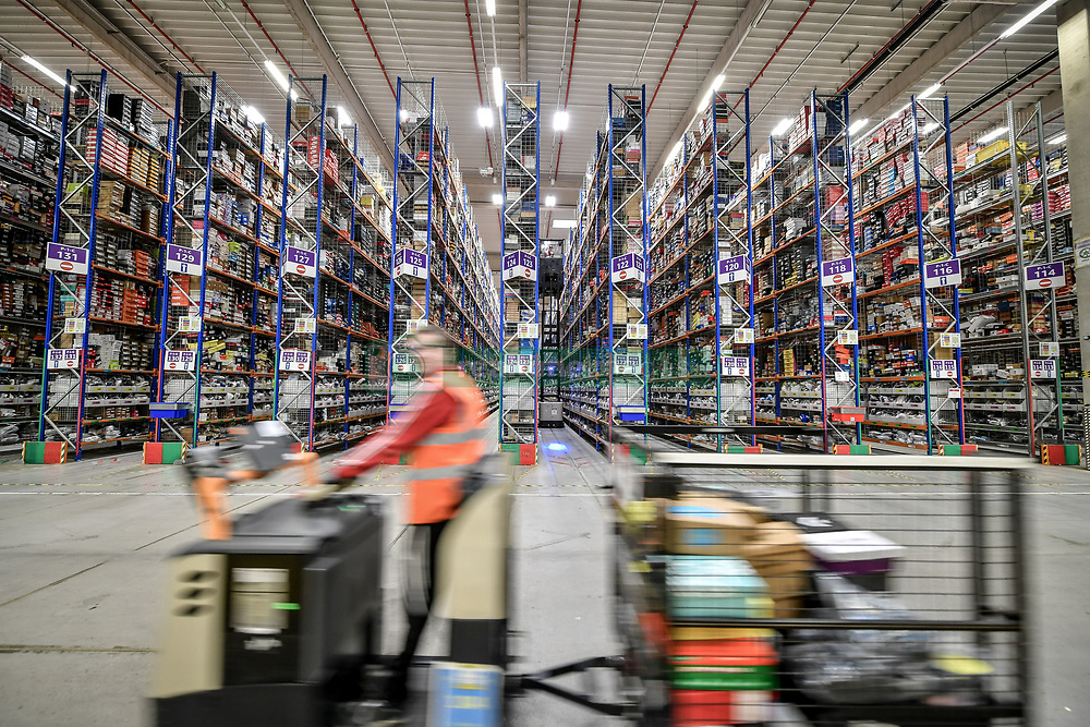 A worker on a motorised trolley passes thousands of items on high level racking at Amazon's fulfillment centre in Swansea, in the run up to Black Friday.