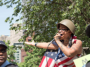 An anti-Sharia law protester stretches her tattooed arm out and wears and army helmet while talking into a microphone