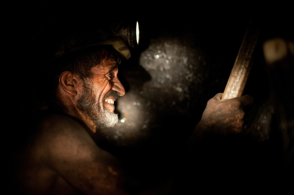 A miner works in total darkness with primitive equipment in the Karkara coal mine.