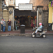Dressed for Mardi Gras, she uses her scooter to negotiate the French Quarter streets.