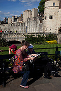 Tourists at the Tower of London on a sunny June day. Her Majesty's Royal Palace and Fortress, more commonly known as the Tower of London, is a historic castle on the north bank of the River Thames in central London, England. It lies within the Tower Hamlets, separated from the eastern edge of the City of London by the open space known as Tower Hill. It was founded towards the end of 1066 as part of the Norman Conquest of England. The White Tower, which gives the entire castle its name, was built by William the Conqueror in 1078, and was a resented symbol of oppression, inflicted upon London by the new ruling elite. The castle was used as a prison since at least 1100, although that was not its primary purpose. A grand palace early in its history, it served as a royal residence. As a whole, the Tower is a complex of several buildings set within two concentric rings of defensive walls and a moat. There were several phases of expansion, mainly under Kings Richard the Lionheart, HenryIII, and EdwardI in the 12th and 13thcenturies. The general layout established by the late 13thcentury remains despite later activity on the site.
