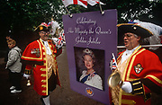 Two toastmasters ring their bells while carrying a large board featuring Queen Elizabeth during the monarchs Golden Jubilee celebrations, on 3rd June 2002, in London, England.