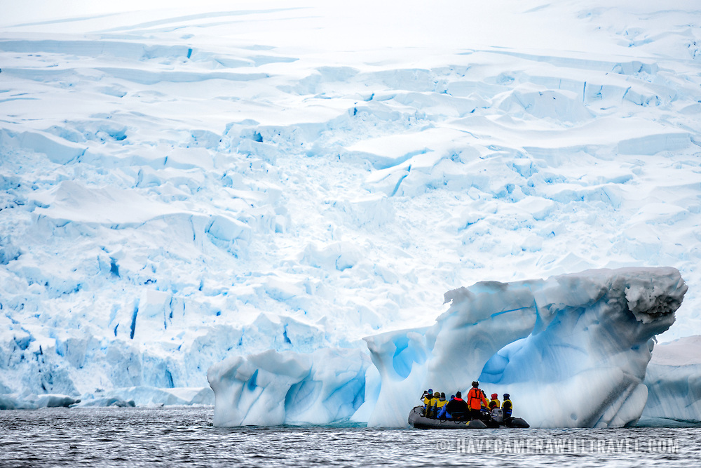 A group of tourists in an inflatable boat investigate a low-lying iceberg in Curtis Bay, Antarctica.