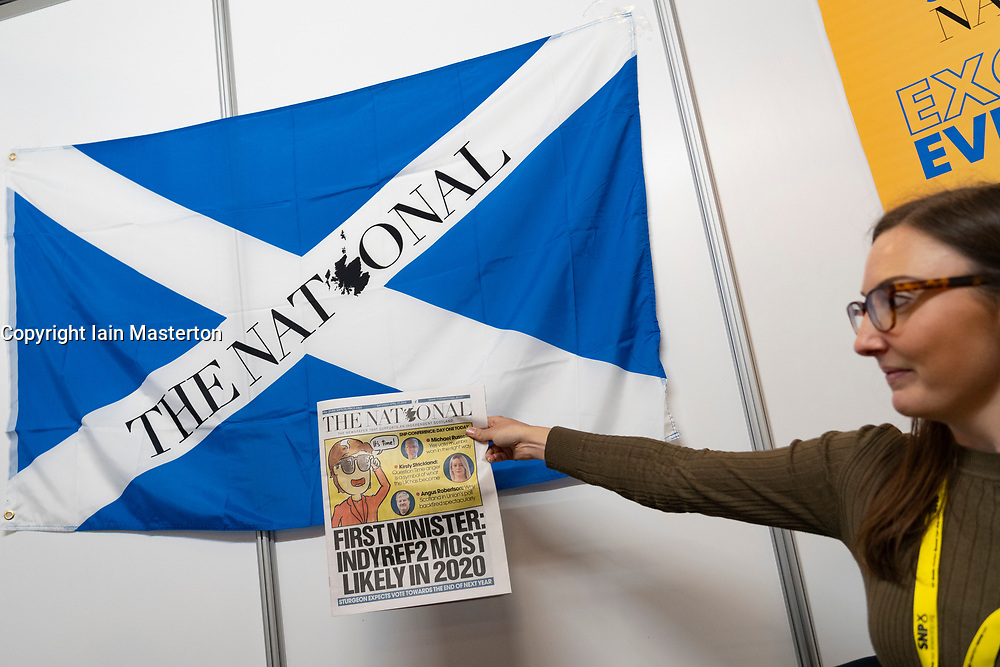 Edinburgh, Scotland, UK. 27 April, 2019. SNP ( Scottish National Party) Spring Conference takes place at the EICC ( Edinburgh International Conference Centre) in Edinburgh. Pictured; Person at The National pro independence newspaper holding newspaper in front of Scottish Saltire flag./