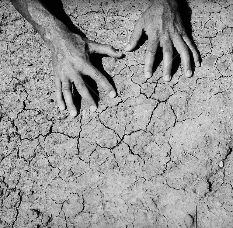 Human hands on cracked land