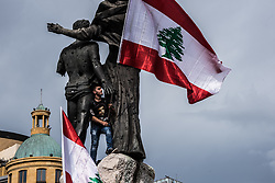 November 22, 2018 - Beirut, Lebanon - A protester seen standing next to statues while holding a flag during the protest.The mood was generally deflated as a handful of protesters, almost outnumbered by journalists were gathered at the Martyrs' Square in Beirut to protest against the poor state of their country, from waste management to the economy, for which they blame the government. Several said that celebrating independence under such circumstances feels like a bad joke. They admit that things will change for the better, saying Lebanese people would protest more, but they're tired because nothing has happened. (Credit Image: © Elizabeth Fitt/SOPA Images via ZUMA Wire)